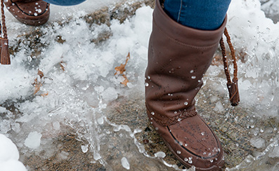 Woman wears mukluk boots in the snow standing by a frozen lake