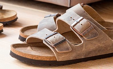 Close up of a pair of tobacco coloured Birkenstock Arizona sandals sitting on a wooden floor.