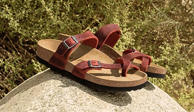 A pair of Havana oiled Gizeh style Birkenstock sandals on a white background.