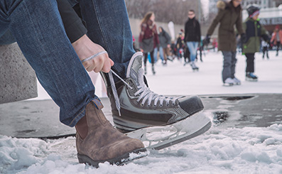 man wearing blundstone boot tightens the laces of his ice skate