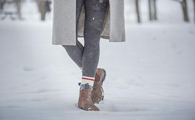 woman wearing brown blundstone boots while walking through snow