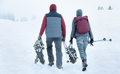 couple wearing keen boots walk together through the snow carrying ski gear