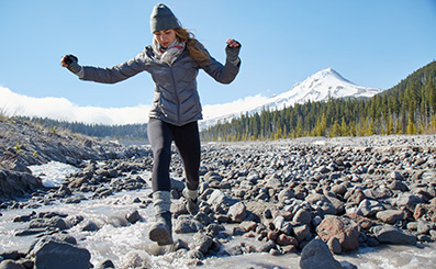 woman wearing keen boots leaps across rocks near a river in the winter