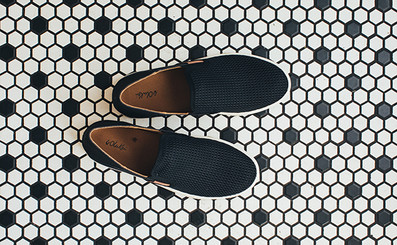 Ladies black leather slip on Pehuea shoes resting on a floor of black & white tiles.
