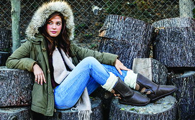 A woman wearing a parka sits with her Bearpaw boots resting on a stack of cut logs
