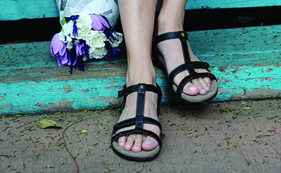 Black women's Taos sandals on wooden stairs